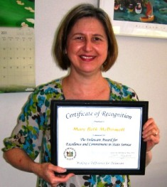Photo of MaryBeth McDermott holding up the Governor's Award for Excellence and Commitment in State Service